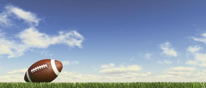 American football on grass; fluffy couds at the background